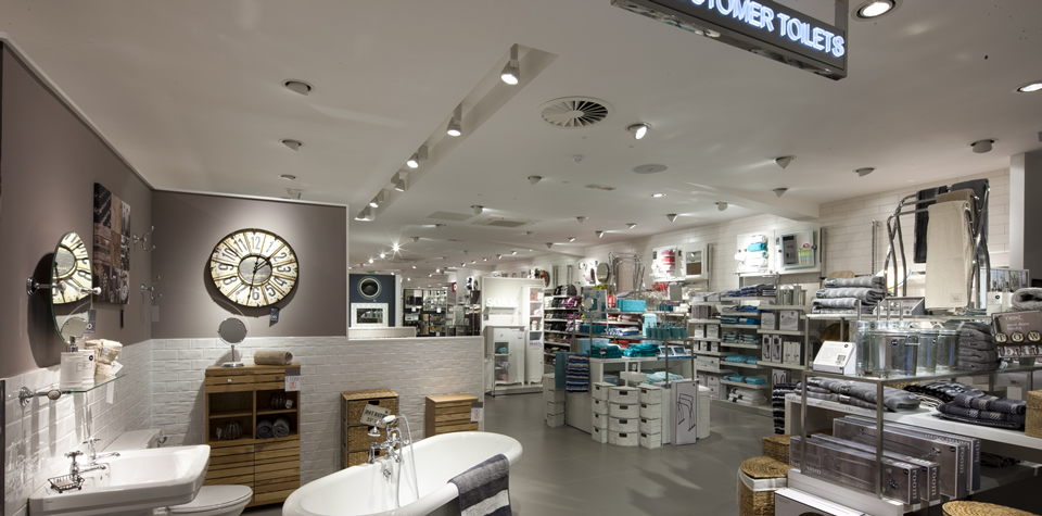 An image of the homeware department in Next, showing MF plasterboard ceilings and lay-in grid suspended ceilings, installed by Construction Interior Design.