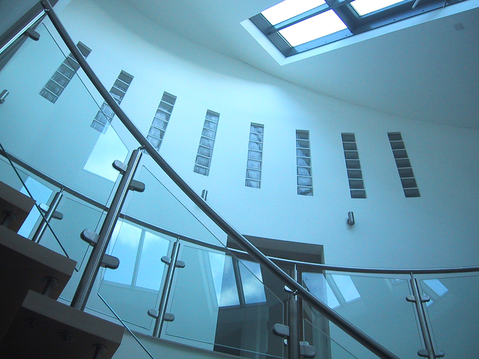 An image of a spiral stairwell with sky lights and interior windows, designed by Construction Interior Design.
