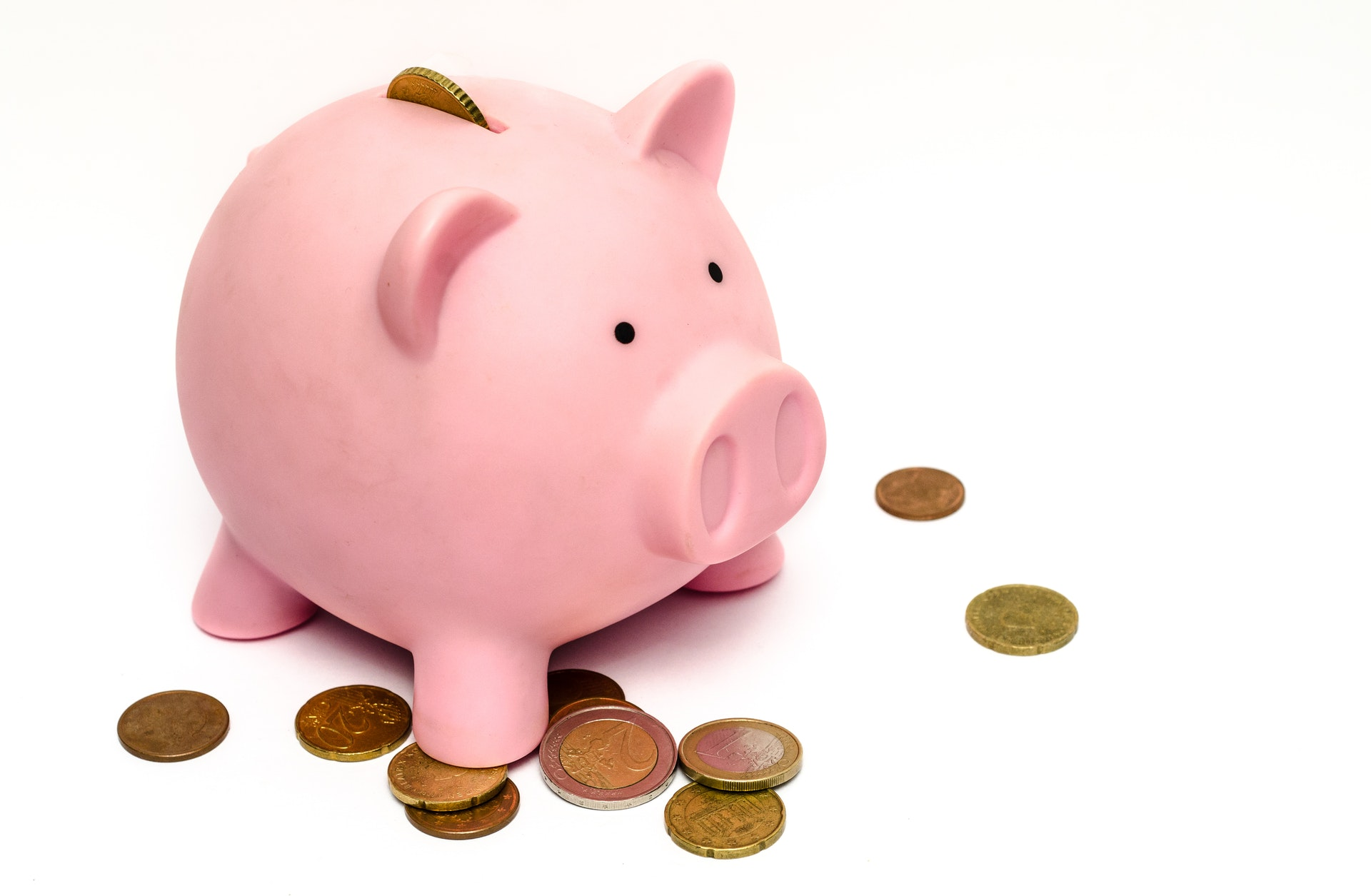 An image of a piggy bank with coins around it